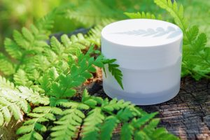 Cosmetic cream for skin care. Natural cosmetics in nature with green fern leaves