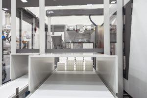 Da die Nesteinsätze aus POM nicht unmittelbar nach dem Entformen gestapelt werden können, installierte der Maschinenbauer ein U-förmiges Förderband oberhalb der Produktionszelle als Nachkühlstrecke. Von dort aus nimmt der Roboter die Teile auf und taktet sie über das größere untere Förderband aus.