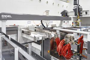 Die Linearroboter nehmen zwei Aufgaben wahr: das Entformen der Spritzgießteile aus dem Werkzeug und das Umsetzen der abgekühlten Teile von der Nachkühlstrecke aufs Austaktban.