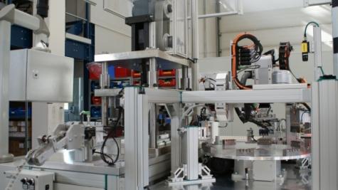Von links unten wird das umspritzte Stanzband in das Austrennwerkzeug geführt und dann kommen jeweils vier Stecker zu den Prüfstationen am Rundschalttisch.
