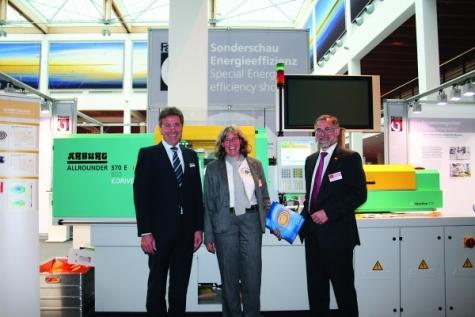 Von links: Herbert Kraibühler, Dr. Anka Bernnat und Dr. Reinhard Jakobi vor der Spritzgießmaschine auf der Fakuma. Bild: Redaktion Plastverarbeiter
