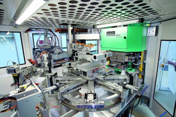 Blick in den gekapselten Produktionsraum der Fertigungszelle: Im Vordergrund die Dreheinheit mit den befüllten Moldbars. (Bildquelle: Arburg)