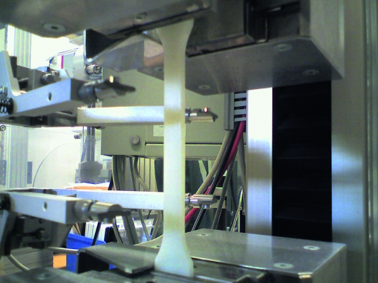 In der Mitte der Versuchsanordnung sieht man den unter Spannung  stehenden Probestab in der Zugprüfmaschine. (Bildquelle: Flir Systems)