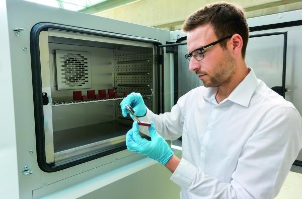 Ein Mitarbeiter des Fachgebiets Maschinenelemente  der TU Dortmund überprüft die Maßänderungen der im  Konstantklimaschrank eingelagerten Proben. (Bildquelle: TU Dortmund)